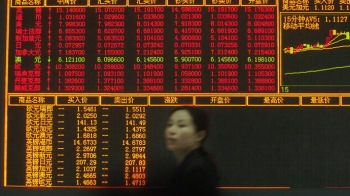 A woman walks past an electronic board showing exchange rate information at a bank in Ningbo, east C..